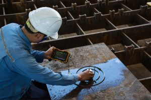 In hose specialist inspecting the steel plate so to detect any defects or imperfection